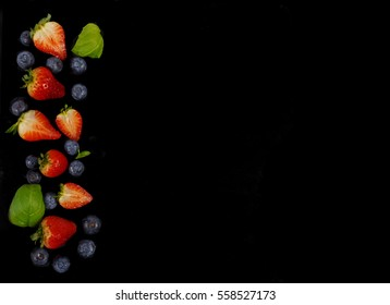 Strawberries, blueberries and basil on a blackboard with space for copy.