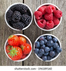 strawberries, blueberries, blackberries and raspberries in bowls, top view, close-up