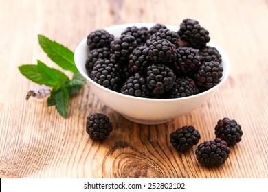 strawberries, blueberries, blackberries and raspberries in bowls, top view, close-up. Selective focus.