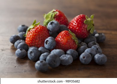 strawberries and blueberries on the wood table