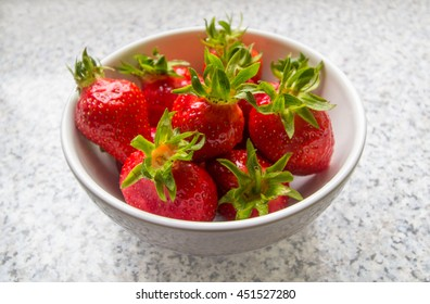 Strawberries in a bowl in an angled view on a kitchen table