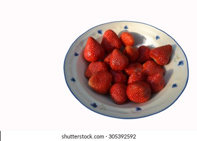 Strawberries in bowl in front on white background