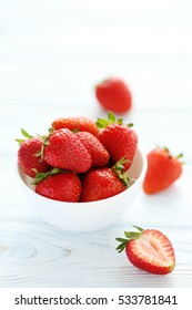Strawberries in bowl on white wooden table