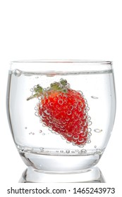 Strawberries with bubbles in a glass on a white background
