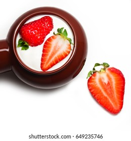 Strawberries in a ceramic cup with sour cream. Strawberry berries are isolated. A group of objects. Isolate. Breakfast, healthy food