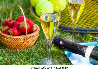 Strawberries, champagne and tennis balls on racket in the grass