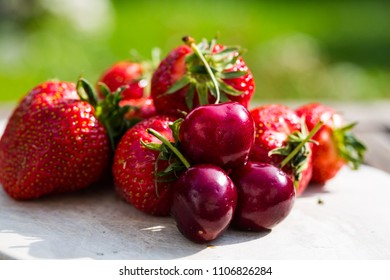 Strawberries and cherries together, green background