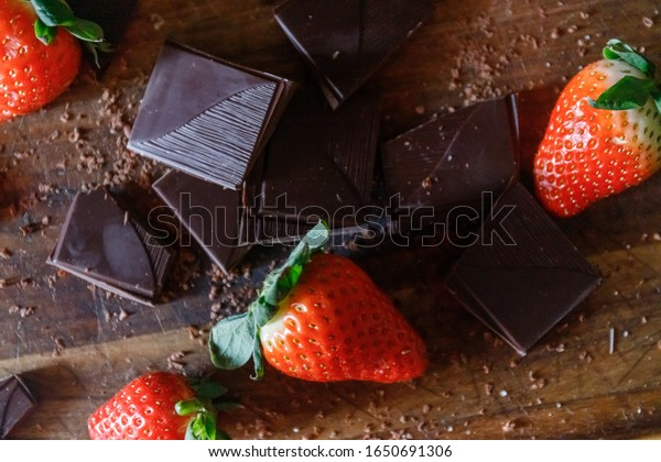 Strawberries and chocolate on a wooden cutting board. Fresh berries with pieces of dark chocolate, ingredients for a birthday cake.