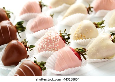 Strawberries covered in chocolate on a white wooden table