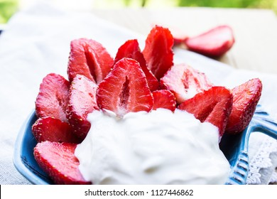 Strawberries with cream in a ceramic bowl. Close-up. Selective focus.