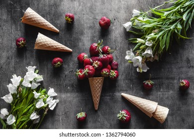 Strawberries in cups on a dark gray background with waffles and white flowers. Healthy food, fruit