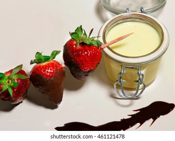 strawberries with custard in glass and chocolate