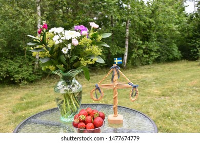 Strawberries, flowers and a small maypole on a table outdoors in a green garden