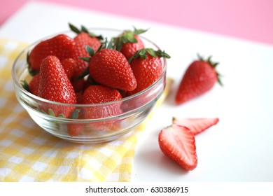 Strawberries in a glass bowl isolated on pastel pink background