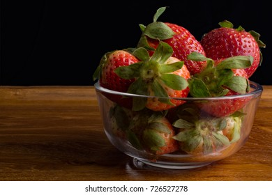 Strawberries in glass bowl on wooden tray against black background.