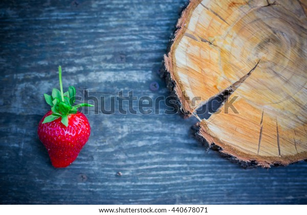 Strawberries with green leaves on a textured board