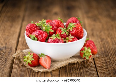 Strawberries as high detailed close-up shot on a vintage wooden table; selective focus