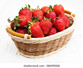 Strawberries with leaves on a wooden background