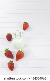 Strawberries and milk on wooden pink background with space for text
