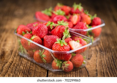 Strawberries on an old wooden table as detailed close-up shot; selective focus