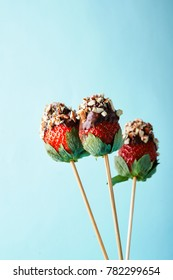 strawberries on sticks with chocolate and nuts on blue background