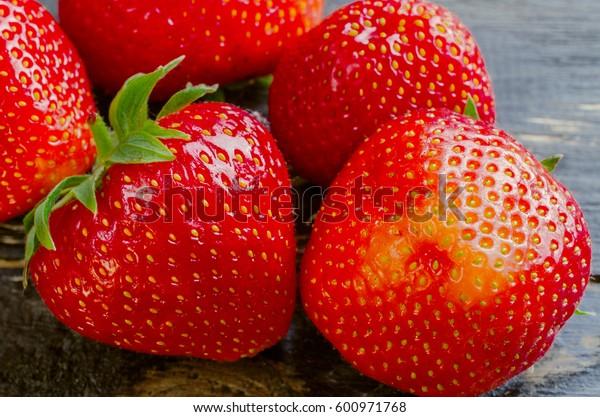 Strawberries on wooden dark background close-up.