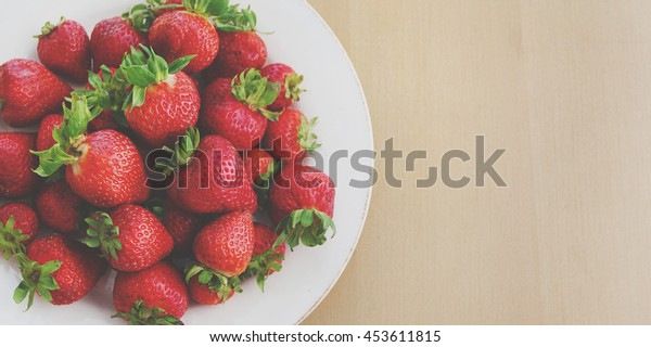 Strawberries on wooden table.