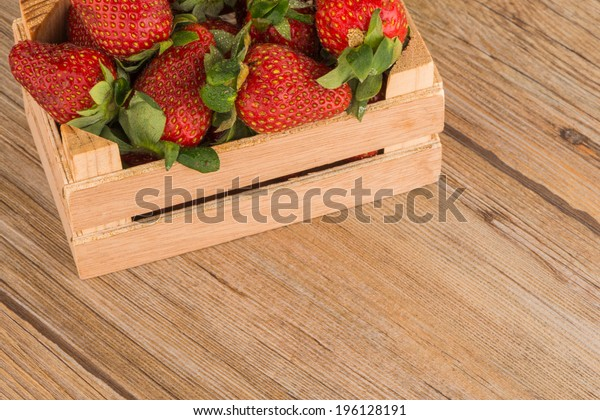 Strawberries over odl brown wooden table background