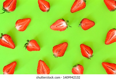 Strawberries pattern close up. Bright pattern of fresh cut in half strawberry on light green background. Top view, flat lay.