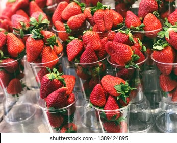 strawberries in plastic glasses for sale on food market in barselona