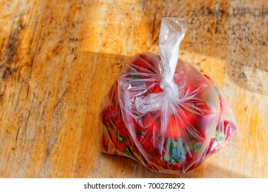 Strawberries in a sack on a wooden table