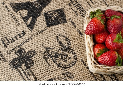 Strawberries in a small basket on the beige jute table cloth with French motif print