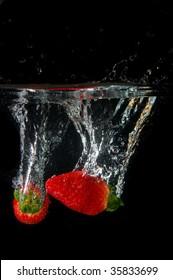 strawberries splashing in fresh water showing healthy lifestyle