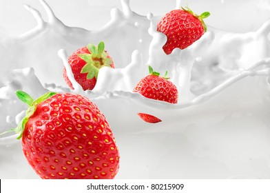 Strawberries splashing in to milk