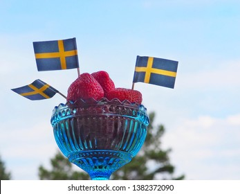 Strawberries and swedish flags. Celebration of Swedens National Day or Midsummer in Sweden.