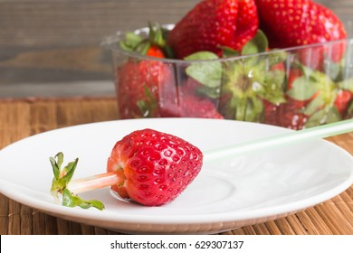 Strawberries in a transparent box on wooden background.