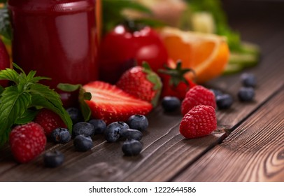 Strawberries and varieties of fruits, a bottle of fresh strawberry juice on wooden background