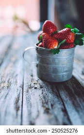 strawberries in a vintage cup on a wooden background