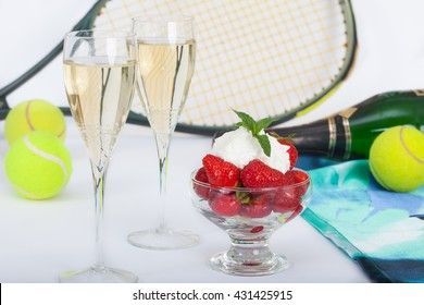 Strawberries with whipped cream and champagne, tennis racket and balls on table in background