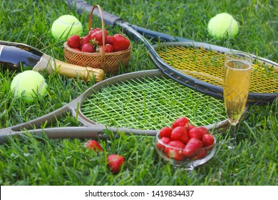 Strawberries with whipped cream, glass with champagne and tennis rackets and balls on grass. Wimbledon Grand slam tennis concept.