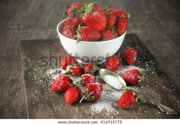 Strawberries in white bowl with granulated sugar on vintage wooden board.