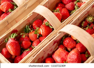Strawberries in wooden baskets at the market with a shallow depth of field.