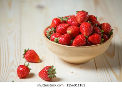 Strawberries in wooden bowl. Fresh nice strawberries on wooden table. Juice strawberry