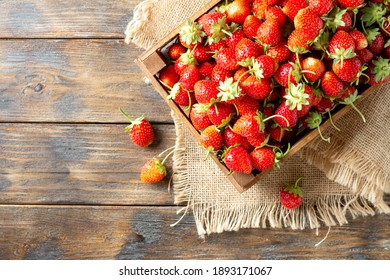 Strawberries in a wooden box on a brown wooden background