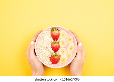 Strawberry banana smoothie bowl in woman hands on yellow background. Bright,  colorful and healthy food concept. Flat-lay, top view. Copy space for your text.