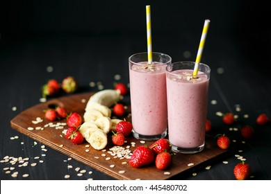 Strawberry and banana smoothie in the glass on black background