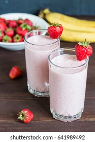 Strawberry banana smoothie healthy breakfast drink in glass on dark wooden background. Delicious food healthy lifestyle vertical photo