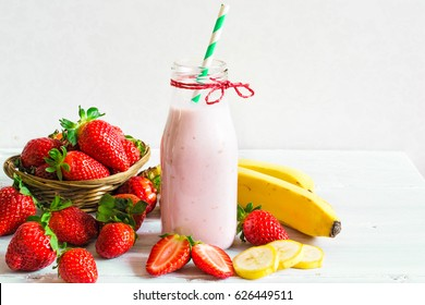 Strawberry and banana smoothie or milkshake with a straw in a bottle with fresh berries on white wooden background. healthy food for breakfast and snack