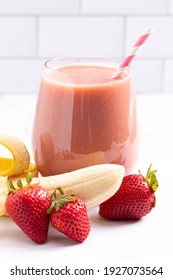 A Strawberry Banana Smoothie on a Bright White Kitchen Cabinet