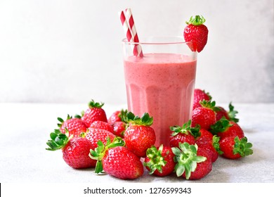 Strawberry banana smoothie in a tall glass on a light slate, stone or concrete background.